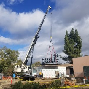Photo of skid being lifted by a crane into place on the UC Davis campus