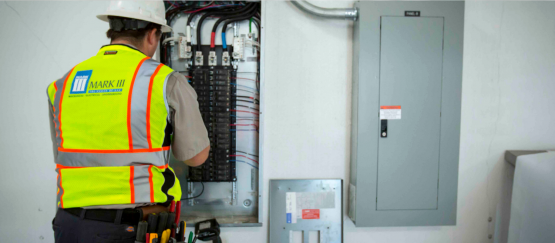 Commercial Electrician works on electrical breaker